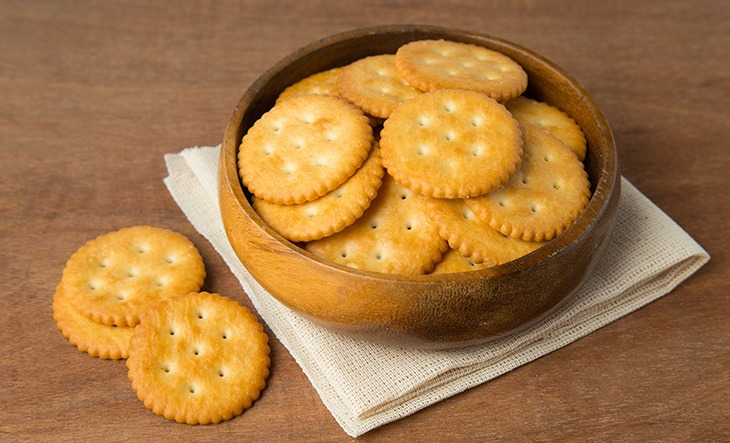 Round salted cracker cookies in wooden bowl