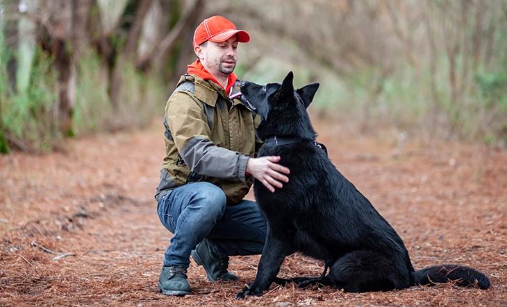 Black German shepherd with its owner in the park