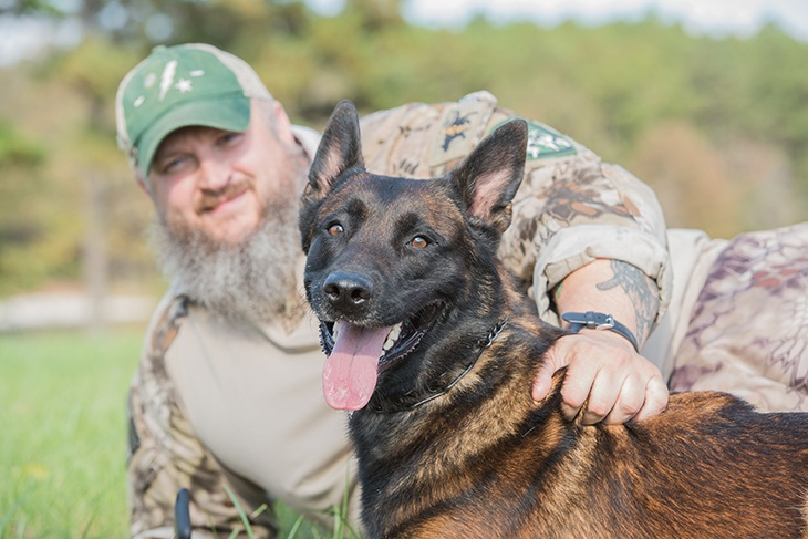 Belgian malinois dog being held by his partner that is blurred
