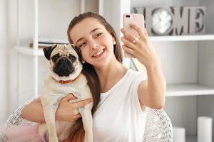 Teenage girl taking selfie with cute pug dog at home